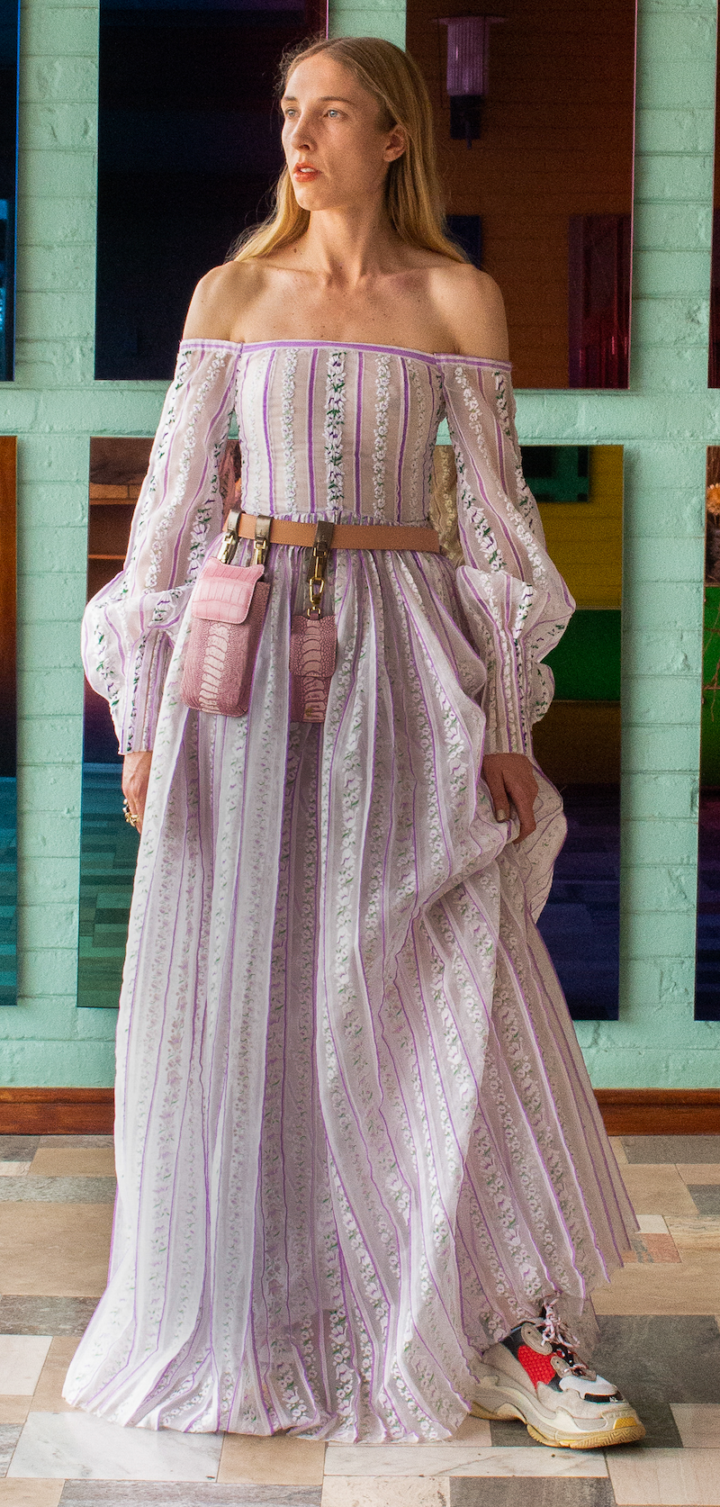 Woman wearing a lilac embroidered off-the-shoulder full length, long sleeved dress