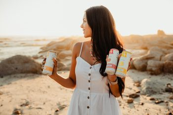 Woman holding A1 fruit Water cans on beach